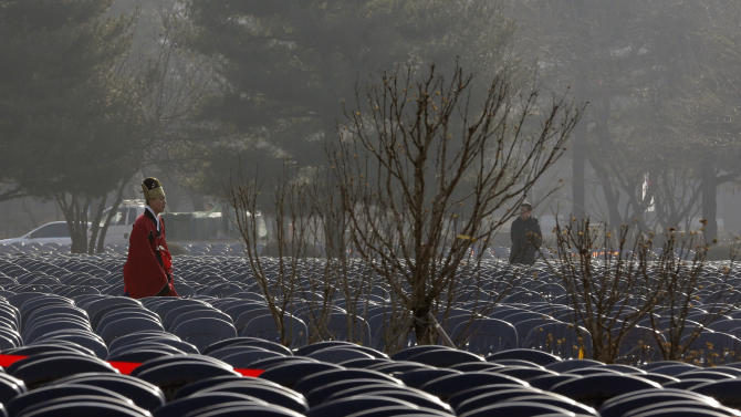 A South Korean soldier, wearing a traditional uniform, walks through a sea of chairs arranged at the National Assembly during a rehearsal on the eve of President-elect Park Geun-hye's inauguration in Seoul, South Korea, Sunday, Feb. 24, 2013. (AP Photo/Lee Jin-man)