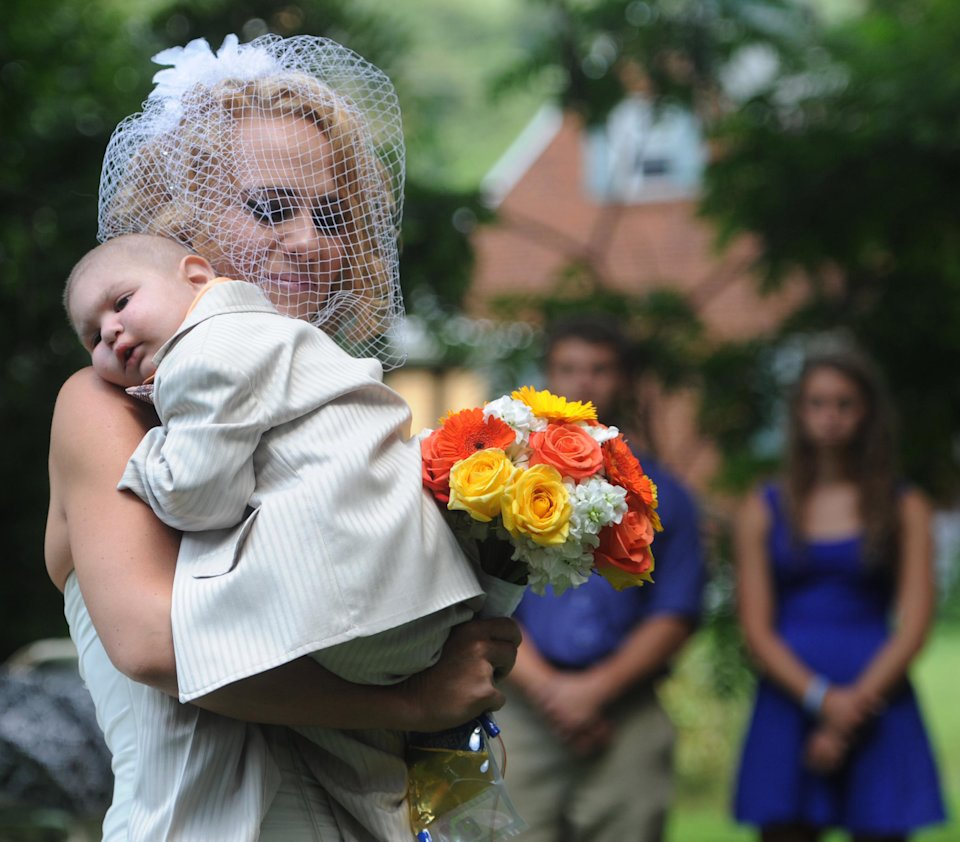 FILE - This Aug. 3, 2013 file photo, Christine Swidorsky carries her son and the couple's best man, Logan Stevenson, 2, down the aisle to her husband-to-be Sean Stevenson during the wedding ceremony in Jeannette, Pa. Christine Swidorsky Stevenson says on her Facebook page that Logan died in her arms at 8:18 p.m. Monday, Aug. 5, 2013, at their home in Jeannette, about 25 miles east of Pittsburgh. Logan, who was born Oct. 22, 2010, was diagnosed shortly after his first birthday with acute myeloid leukemia. The Stevensons abandoned an original wedding date of July 2014 after learning from doctors late last month that their son had two to three weeks to live. The couple wanted Logan to see them marry and to be part of family photos. (AP Photo/Tribune Review, Eric Schmadel)