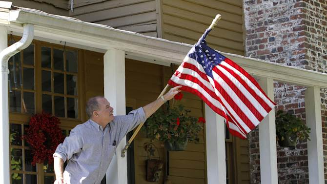 This photo taken Oct. 10, 2012 shows Virginia voter Harry Donahue adjusting an American flag on the front porch of his farmhouse, built in the 1700's, in Farmville, Va.  Donahue, a 68-year-old retired chemical worker from Philadelphia's New Jersey suburbs, moved to Virginia in 2001 and brought with him an independent streak and a voting pattern that ranges from Ronald Reagan to Ross Perot. He plans to back Obama this year after supporting John McCain in 2008.  (AP Photo/Steve Helber)