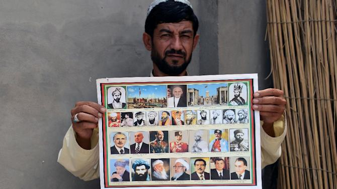 A man holds a calendar bearing the images of Afghan leaders including the Taliban's late chief Mullah Omar (bottom, 2L) in Kandahar, Afghanistan on July 31, 2015