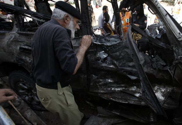 A police official examines a damaged car at the site of a bomb blast in Peshawar
