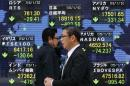 Passersby walk past in front of an electronic board displaying Japan's Nikkei average and various countries' stock price index outside a brokerage in Tokyo