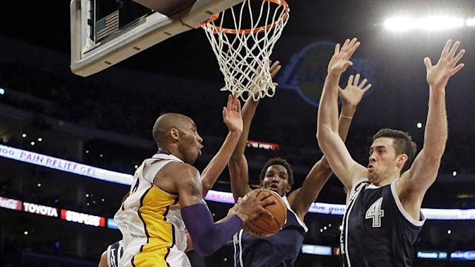 Los Angeles Lakers guard Kobe Bryant (24) passes as Oklahoma City Thunder center Hasheem Thabeet, center, and forward Nick Collison (4) defend in the first half of an NBA basketball game in Los Angeles, Sunday, Jan. 27, 2013. The Lakers won 105-96. (AP Photo/Reed Saxon)