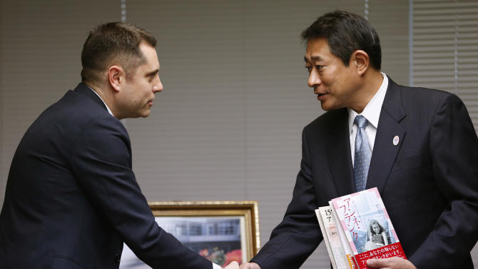 """Israeli Embassy to Japan representative Peleg Lewi, left, shakes hands with Suginami Ward Mayor Ryo Tanaka as he hands over Anne Frank-related books to public libraries at the Suginami Ward Office in Tokyo Thursday, Feb. 27, 2014. The Israeli Embassy is donating 300 books after the recent vandalism of a similar number of such books in their collections. More than 300 books related to Anne Frank, including copies of """"The Dairy of a Young Girl,"""" have been found damaged in Tokyo libraries. Suginami was particularly hard hit with 121 books vandalized. (AP Photo/Shizuo Kambayashi)"""