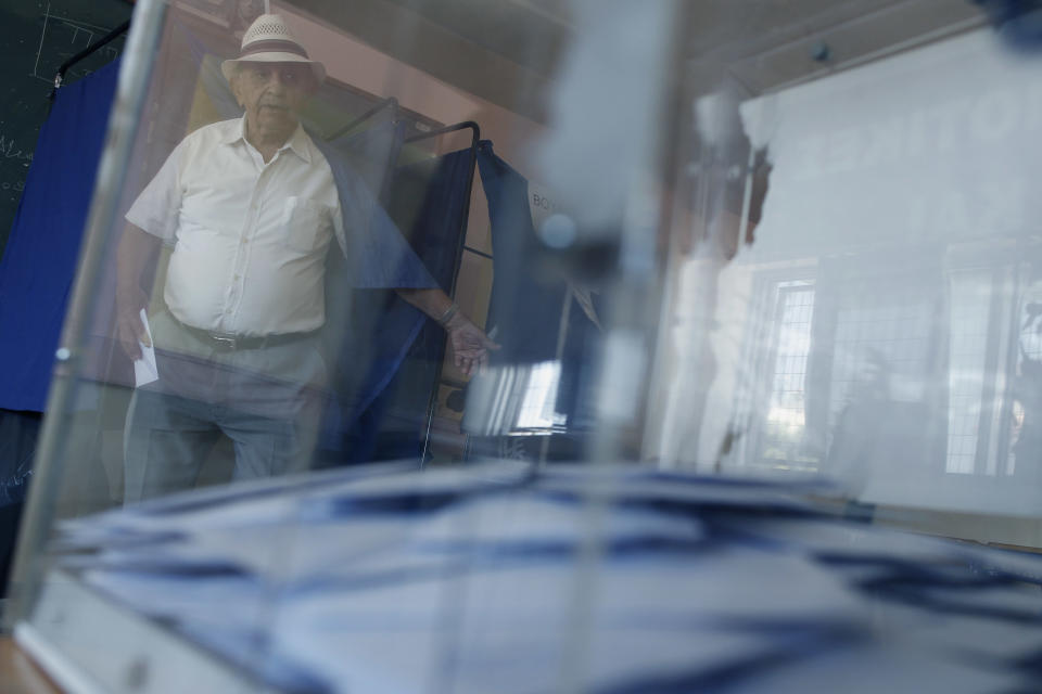 A man exits a booth before casting his ballot at a polling station in Athens, Sunday, June 17, 2012. Greeks are voting Sunday for the second time in six weeks in what is arguably their country's most critical election in 40 years. (AP Photo/Petros Giannakouris)