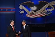 US President Barack Obama (R) and Republican presidential candidate Mitt Romney (L) end the first presidential debate at Magness Arena at the University of Denver in Denver, Colorado