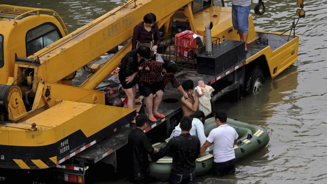 Man holds baby as they get onto a raft pushed by rescuers on a flooded street after Typhoon Fitow hit Yuyao