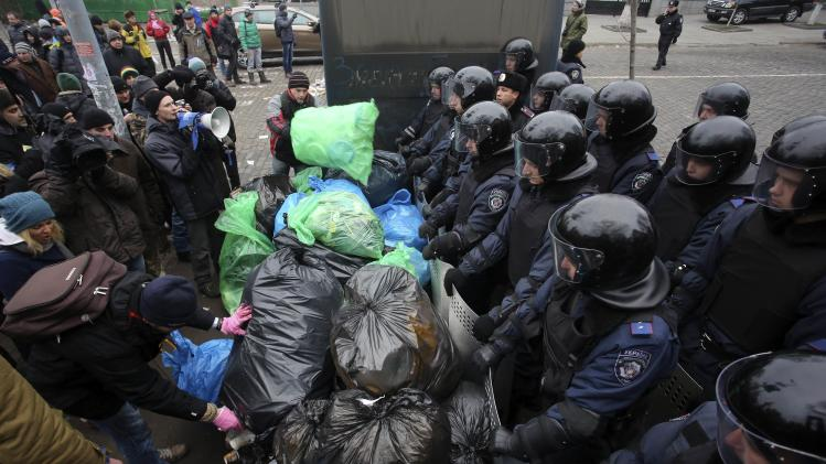 Pro-European integration protesters pile up garbage bags in front of riot police officers in Kiev
