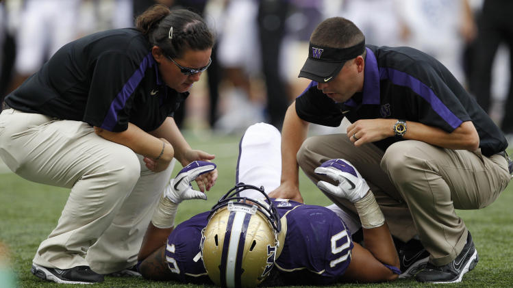 Medical personnel tend to injured Washington player John Timu in the second half of an NCAA college football game, Saturday, Sept. 24, 2011, in Seattle. Timu left the field in an ambulance. Washington won 31-23. (AP Photo/Elaine Thompson)