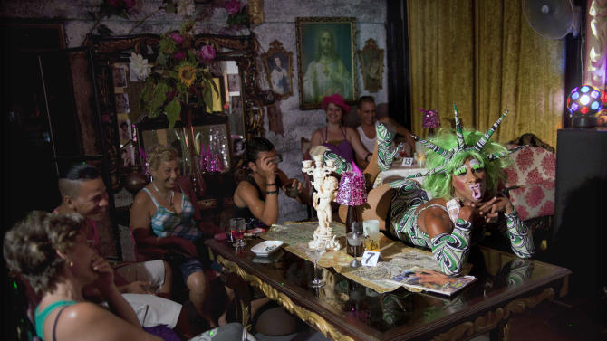"""In this May 15, 2013, Yanolis Carrero, 27, right, a gay transvestite artist known as """"Blanquita,"""" performs on a table top during a drag show at the Fashion Bar Havana, in Havana, Cuba. A week of drag shows, colorful marches and social and cultural events in Havana culminates Friday with celebrations of the International Day Against Homophobia. Gays were persecuted for decades after the 1959 Cuban Revolution, sometimes sent to grueling rural work camps along with others considered socially suspect by the Communist government. But there has been a gradual shift away from macho attitudes, and Fidel Castro himself has publicly regretted the mistreatment of people seen as different. (AP Photo/Ramon Espinosa)"""