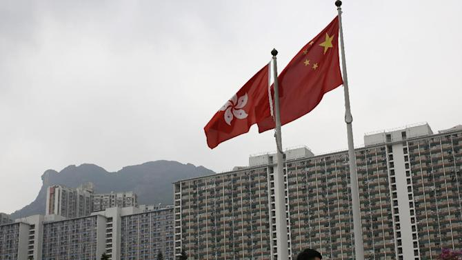 "A Hong Kong flag, left, and a Chinese national flag appear in front of a yellow banner, upper left, with the words ""I want genuine universal suffrage"" in Chinese and ""Umbrella Movement"" in English hanging from the face of Lion Rock mountain in Hong Kong Thursday, Oct. 23, 2014. Democracy activists hung the banner on the mountain in support of the protest movement in which thousands of demonstrators have camped out on the streets of the southern Chinese financial center for nearly a month to press their demands for greater democracy. (AP Photo/Vincent Yu)"