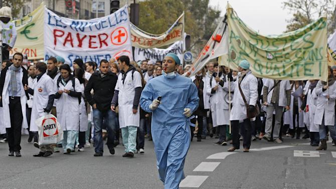 Hundreds of French doctors, many wearing white lab coats and blue surgical caps,  march in Paris Monday Nov 12 2012 in a protest over work conditions and government proposals that aim to limit how much doctors charge above the state insurance system's reimbursements. Many doctors complain of being overworked and fear a slide toward free-market, American-style health care.  (AP Photo/Remy de la Mauviniere)