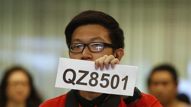A Changi Airport staff holds up a sign to direct possible next-of-kins of passengers of AirAsia flight QZ 8501 from Indonesian city of Surabaya to Singapore, at Changi Airport in Singapore