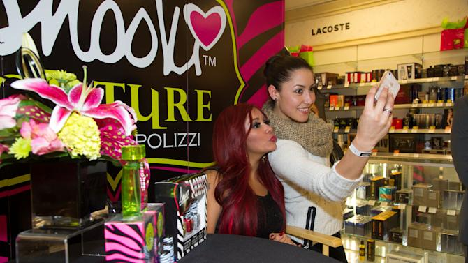 """Nicole """"Snooki"""" Polizzi takes photos with fans during a meet and greet at a Perfumania for the release of her second fragrance, """"Snooki Couture"""" on Wednesday, January 9, 2013, in Las Vegas, NV (Photo by Al Powers/Powers Imagery/Invision/AP)"""