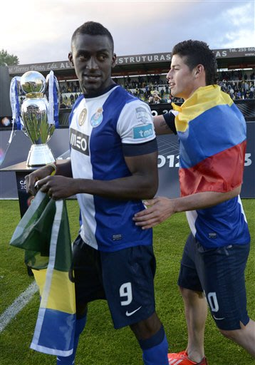 FC Porto's Jackson Martinez, left, and James Rodriguez, both from Colombia, walk past the trophy after their 2-0 victory over Pacos Ferreira in the last match of the Portuguese League soccer season at