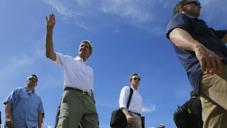 U.S. Secretary of State Kerry walks back to his motorcade after touring the damage from super typhoon Haiyan in Tacloba
