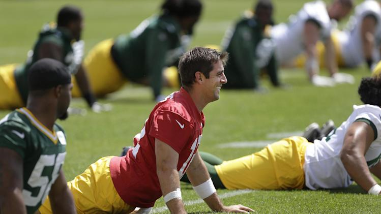 Green Bay Packers quarterback Aaron Rodgers stretches during NFL football minicamp Tuesday, June 17, 2014, in Green Bay, Wis