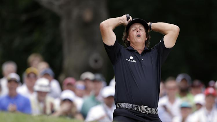 Phil Mickelson reacts after hitting out of a bunker on the second hole during the fourth round of the U.S. Open golf tournament at Merion Golf Club, Sunday, June 16, 2013, in Ardmore, Pa. (AP Photo/Darron Cummings)