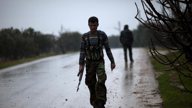 A Free Syrian Army fighter walks to meet his comrades as the Syrian Army  advances towards the town of Sarmin, north Syria, Monday, Feb. 27, 2012. European Union foreign ministers said Monday they were increasingly appalled by the Syrian government's ruthless campaign of repression against civilians, and imposed new sanctions in hopes of pressuring the regime to change course. (AP Photo/Rodrigo Abd)