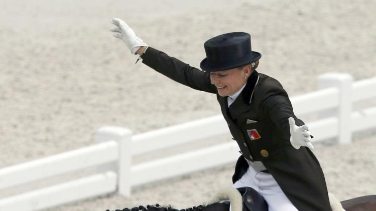 Switzerland's Susmelj, riding Smeyers Molberg, celebrates with her horse during the Individual Dressage Grand Prix Competition at the World Equestrian Games at the d'Ornano stadium in Caen