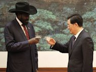 Chinese President Hu Jintao (right) and South Sudan President Salva Kiir toast after a signing ceremony at the Great Hall of the People in Beijing on April 24, 2012. Kiir will cut short his visit to China due to &quot;domestic issues&quot;, a Chinese official said Wednesday, as violence between the world&#39;s newest nation and Sudan intensified