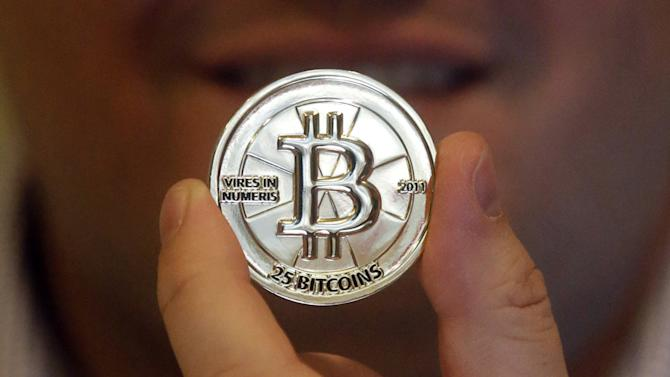 In this April 3, 2013 photo, Mike Caldwell, a 35-year-old software engineer, holds a 25 Bitcoin token at his shop in Sandy, Utah. Caldwell mints physical versions of bitcoins, cranking out homemade tokens with codes protected by tamper-proof holographic seals, a retro-futuristic kind of prepaid cash. With up to 70,000 transactions each day over the past month, bitcoins have been propelled from the world of Internet oddities to the cusp of mainstream use, a remarkable breakthrough for a currency which made its online debut only four years ago. (AP Photo/Rick Bowmer)