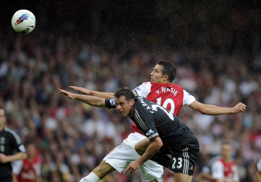 Arsenal's Robin van Persie, right,  jumps for the ball with Liverpool's Jamie Carragher during their English Premier League soccer match at the Emirates stadium, London, Saturday, Aug. 20, 2011. (AP Photo/Tom Hevezi)