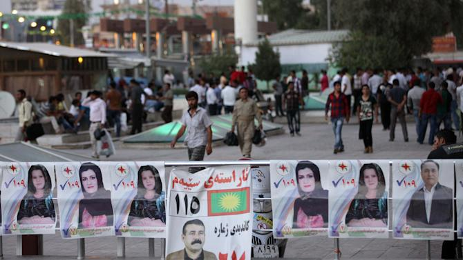 People walk past election campaign posters of different parties, in Irbil, Iraq, 350 kilometers (217 miles) north of Baghdad, Friday, Sept. 20, 2013, a day ahead of the self-ruled northern Kurdish region's fourth election for local parliament since 1992. (AP Photo/ Khalid Mohammed)