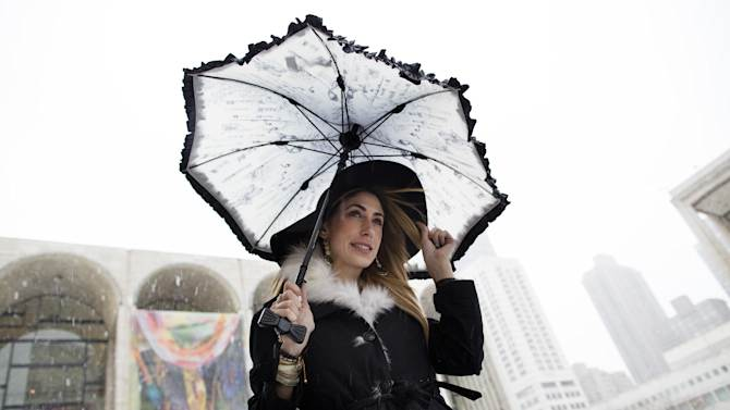 Lauren Rae Levy, of Manhattan, stands outside the Metropolitan Opera House in the snow at Lincoln Center during Fashion Week, Friday, Feb. 8, 2013, in New York. Snow began falling across the Northeast on Friday, ushering in what was predicted to be a huge, possibly historic blizzard and sending residents scurrying to stock up on food and gas up their cars. (AP Photo/John Minchillo)