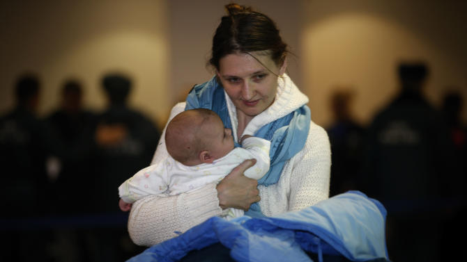 A Russian woman holds her baby while leaving passport control zone just after their arrival from Beirut in Moscow Domodedovo airport, Russia, Wednesday, Jan. 23, 2013. The Kremlin's evacuation of Russians from Syria on Tuesday marks a turning point in its view of the civil war, representing increasing doubts about Bashar Assad's hold on power and a sober understanding that it has to start rescue efforts before it becomes too late.The operation has been relatively small-scale - involving fewer than 100 people, mostly women and children - but it marks the beginning of what could soon turn into a risky and challenging operation.  (AP Photo/Alexander Zemlianichenko)