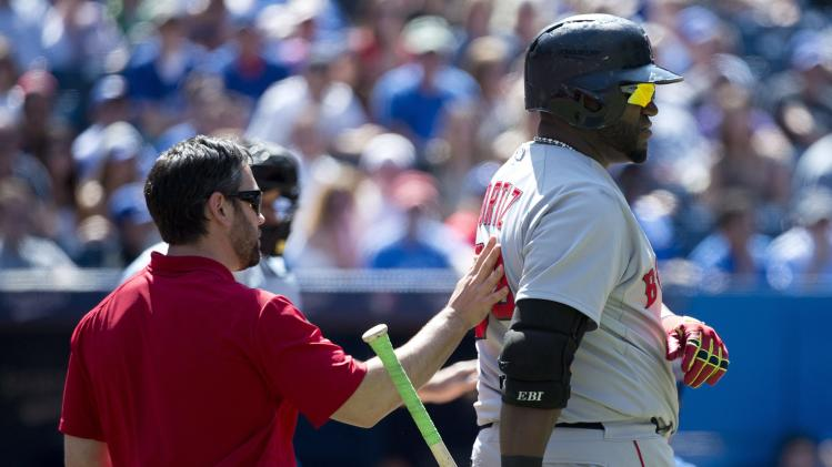 Boston Red Sox' David Ortiz, right, leaves the game with a trainer after injuring himself against the Toronto Blue Jays during the ninth inning of a baseball game in Toronto on Thursday, July 24, 2014. (AP Photo/The Canadian Press, Nathan Denette)