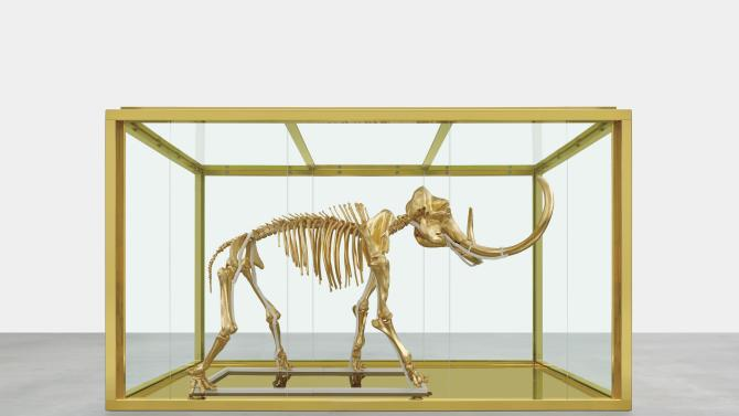 """In this 2014 photo released by Damien Hirst and Science Ltd., British artist Damien Hirst's latest piece entitled """"Gone but Not Forgotten"""", which features the gilded skeleton of a woolly mammoth in a steel and glass vitrine, is displayed. Famed British artist Damien Hirst has created a gilded woolly mammoth skeleton encased in a gold tank to be auctioned off at the annual amfAR Cinema Against AIDS gala in Cap d'Antibes, southern France, on Thursday, May 22, 2014. (AP Photo/Prudence Cuming Associates via Damien Hirst)"""