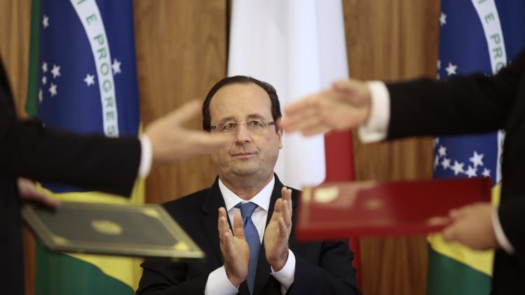 France's President Francois Hollande claps during a signing ceremony at the Planalto Palace in Brasilia