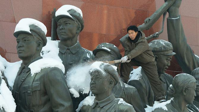 A North Korean man scrapes off snow from the monument of anti-Japanese revolutionary fighters on Mansu Hill in Pyongyang, North Korea Monday, Dec. 10, 2012. North Korea on Monday extended the launch period for a controversial long-range rocket by another week until Dec. 29, citing technical problems. (AP Photo/Kyodo News) JAPAN OUT, MANDATORY CREDIT, NO LICENSING IN CHINA, FRANCE, HONG KONG, JAPAN AND SOUTH KOREA