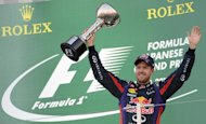 Red Bull driver Sebastian Vettel of Germany holds up the trophy to celebrate his victory in the Formula One Japanese Grand Prix in Suzuka on October 13, 2013
