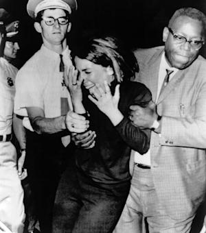 FILE-In this Aug. 21,1964 file photo an overwrought Beatles fan is escorted from the hall during the Beatles second stop of their U.S. tour in Las Vegas, Nevada. To mark the 50th anniversary of the Beatles' only performance in Las Vegas, Cirque du Soleil performers are expected to make surprise, flash mob-style appearances Thursday, Aug. 21, 2014, in the San Francisco and Las Vegas airports and on a flight. (AP Photo)