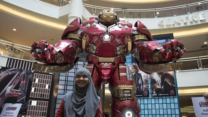 """FILE - In this April 10, 2015 file photo, a Malaysian Muslim woman poses with a Hulkbuster statue from """"Avengers: Age of Ultron"""" at a mall in Kuala Lumpur, Malaysia. Several hundred movie theaters in Germany have refused to screen the new """"Avengers"""" film in a dispute over rental fees with Disney. News agency dpa reported that 686 theaters in 193 mostly small towns refused to show """"Avengers: Age of Ultron,"""" which opened on Thursday, April 23. (AP Photo/Joshua Paul, File)"""
