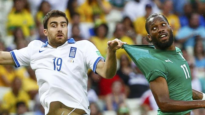 Greece's Papastathopoulos pulls on Ivory Coast's Drogba's jersey during their 2014 World Cup Group C soccer match at the Castelao arena in Fortaleza