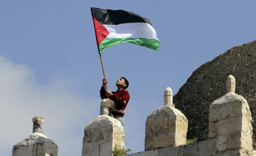 A Palestinian holds a flag during a rally calling on Egyptian authorities to supply the Gaza Strip with fuel and electricity on the southern Gaza Strip