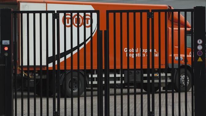 FILE - In this Feb. 21, 2012 file photo a TNT delivery truck is seen behind a closed gate in Hoofddorp, near Amsterdam, Netherlands. United Parcel Service Inc. has ditched its euro5.2 billion (US$6.9 billion) takeover of TNT Express NV after learning that European regulators would reject the deal in its current form. (AP Photo/Peter Dejong, File)