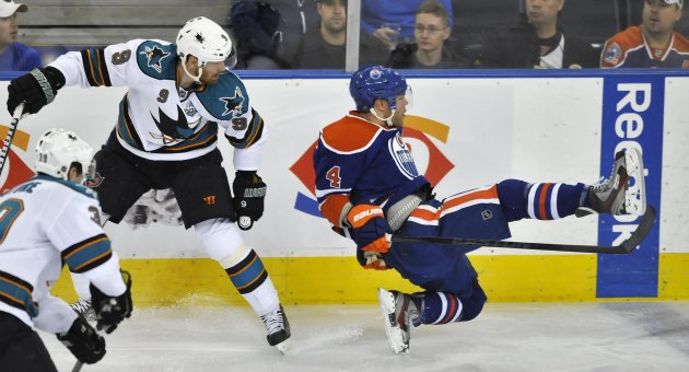 Oilers' Hall goes flying after being hit by Sharks' Havlat during their NHL hockey game in Edmonton