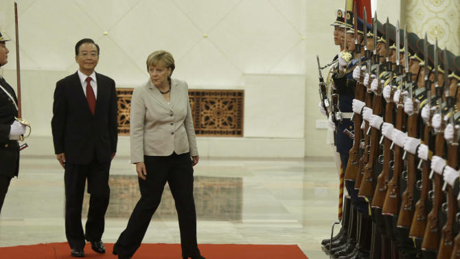 German Chancellor Angela Merkel, center right, and Chinese Premier Wen Jiabao center left, walk together before inspecting a guard of honor during a welcome ceremony at the Great hall of the People in Beijing, Thursday, Aug. 30, 2012. (AP Photo/Ng Han Guan)