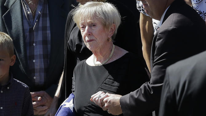 """This photo taken Sept. 19, 2012 shows Barbara Doherty, mother of slain former Navy SEAL Glen Doherty, escorted from the Church of St. Eulalia in Winchester, Mass., after his funeral. What do a Navy mom, Big Bird and AARP have in common? They all want President Barack Obama and Republican Mitt Romney to leave them alone. The two candidates are drawing on personal stories and pop culture references in campaign ads, daily speeches and debate zingers as each seeks to cast himself as an """"everyman"""" and broaden his appeal in the presidential race's closing weeks. But they're encountering resistance at seemingly every turn by a broad collection of people they mention and entities they reference. And this year, the complaints go beyond those that usually occur during campaign years: griping by musical groups whose songs candidates use at rallies.  (AP Photo/Elise Amendola)"""