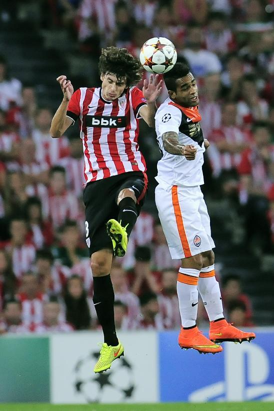 Athletic Bilbao's Ander Iturraspe, left, jumps for the ball with FC Shakhtar Donetsk's Alex Teixeira during the Champions League Group H soccer match between Athletic Bilbao and FC Shakhtar Donetsk at San Mames stadium, in Bilbao, northern Spain, Wednesday Sept. 17, 2014