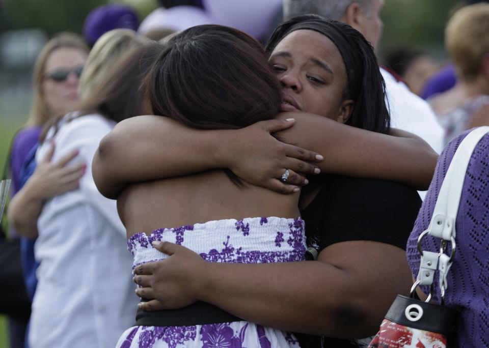 Two people hug Saturday, July 21, 2012, at a vigil at Gateway High School in Aurora, Colo., for AJ Boik, who was a student at the school and who was killed along with 11 others when a gunman opened fire in a movie theater. (AP Photo/Ted S. Warren)