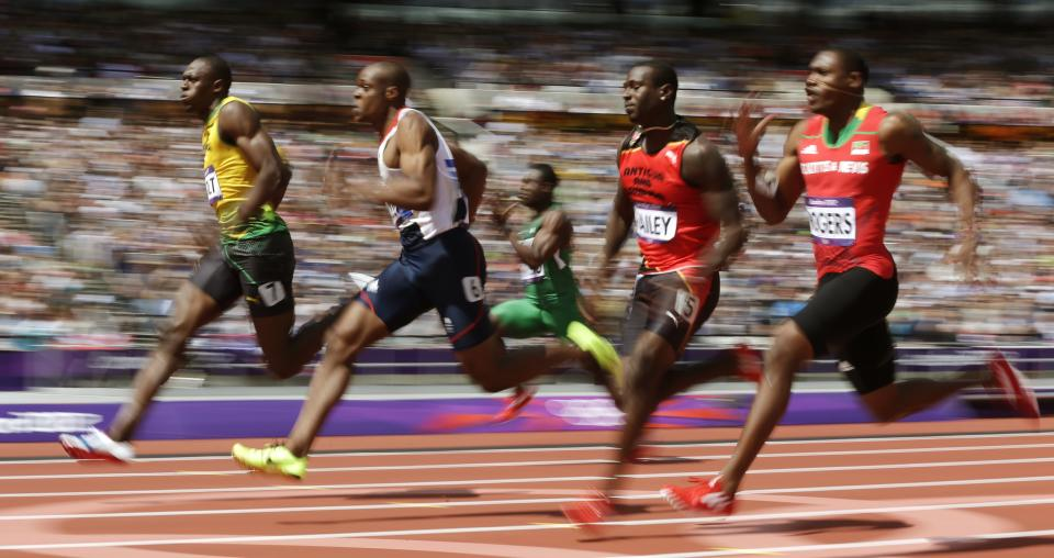 Jamaica's Usain Bolt, left, leads in a men's 100-meter heat during the athletics in the Olympic Stadium at the 2012 Summer Olympics, London, Saturday, Aug. 4, 2012. (AP Photo/David J. Phillip)