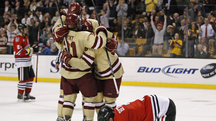 Boston College forward Steve Whitney (21) is surrounded by teammates as he is congratulated on his goal as Northeastern defenseman Anthony Bitetto, right, kneels on the ice during the second period of an NCAA college hockey game at the Beanpot tournament in Boston, Monday Feb. 6, 2012. (AP Photo/Charles Krupa)