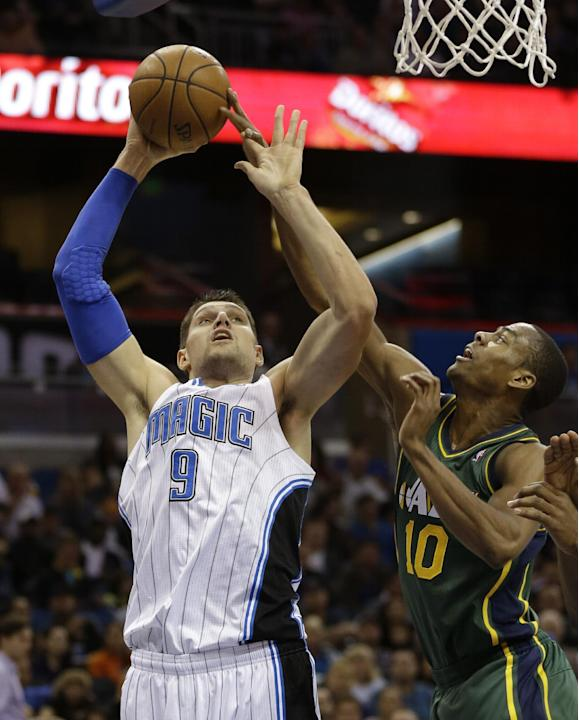 Orlando Magic's Nikola Vucevic (9), of Montenegro, goes up to shoot over Utah Jazz's Alec Burks (10) during the first half of an NBA basketball game in Orlando, Fla., Wednesday, Dec. 18, 2013