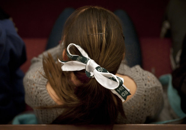 A young woman wears a green and white bow, the colors of Sandy Hook Elementary School, in her hair with the initials of the victims names from the Dec. 14, 2012 shooting during an interfaith a sermon at Newtown Congregational Church in Newtown, Conn., Sunday, Jan. 20, 2013. The Rev. James A. Forbes, Jr., who led one of the country's most prominent liberal Protestant churches, is speaking at the church to honor the victims of last month's school shooting and the legacy of the Rev. Martin Luther King Jr. (AP Photo/Jessica Hill)