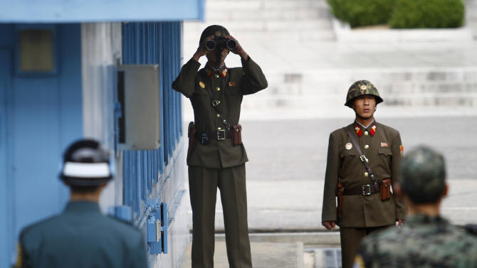 North Korean soldiers, back, look at the southern side as South Korean soldiers, foreground, stand guard at the border village of Panmunjom that separates the two Koreas since the Korean War, in Paju, north of Seoul, South Korea, Tuesday, Oct. 9, 2012. North Korea on Tuesday warned that the U.S. mainland is within range of its missiles, and said Washington's recent agreement to let Seoul possess missiles capable of hitting all of the North shows the allies are plotting to invade the country. (AP Photo/Hye Soo Nah)